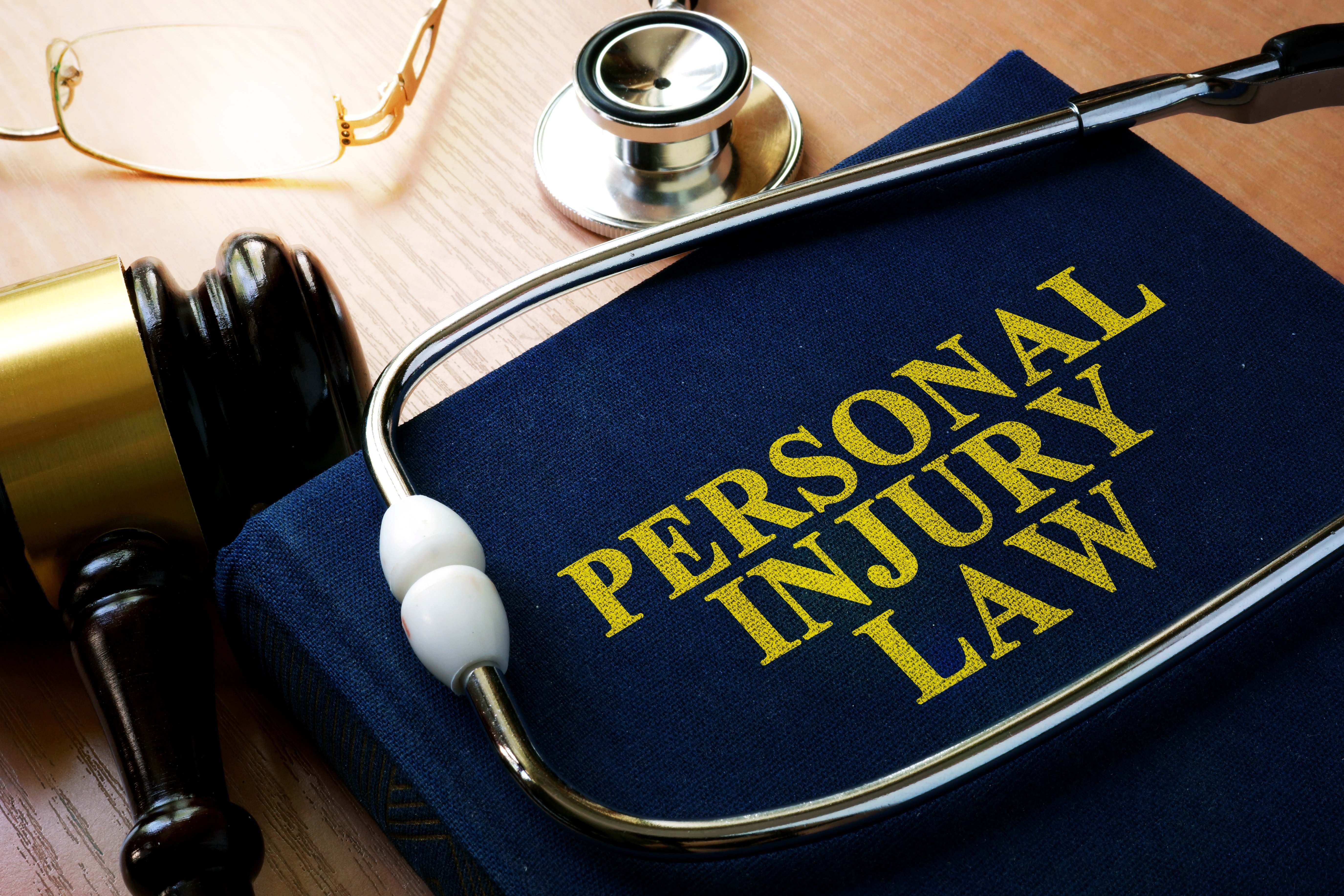 personal injury law book with gavel and stethoscope in foreground